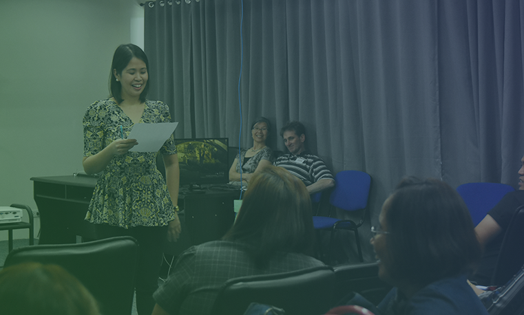 Woman reading a piece of paper in front of her audience