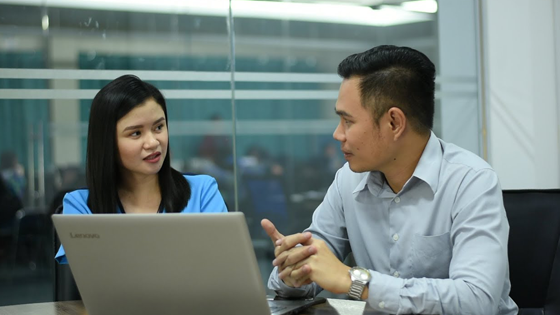 A man and a woman discussing in front of the laptop