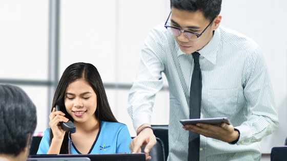 A virtual assistant answering a phone call, beside her is a man holding a tablet